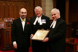 On behalf of his mother, the Honourable Sheila Finestone, Peter Finestone (left) accepts the  2008 Distinguished Service Award from the Senate Speaker, the Honourable Noël Kinsella, Senator (centre) and the Speaker of the House of Commons, the Honourable Peter Milliken, M.P. (right), on May 12, 2008.